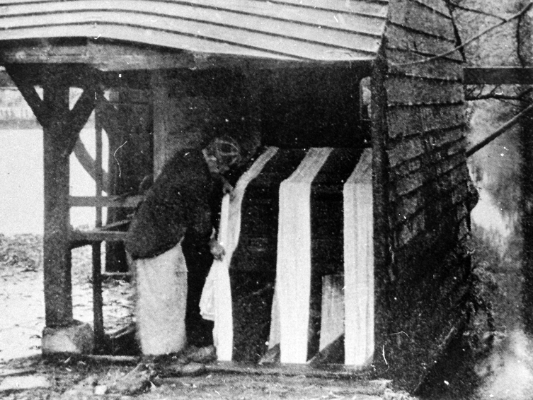 Photo of person washing cloth in hut next to River Wandle